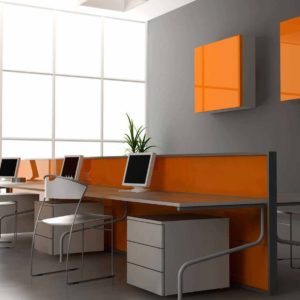 Photo of a modern grey and white office with orange accents. Three workstations are shown.